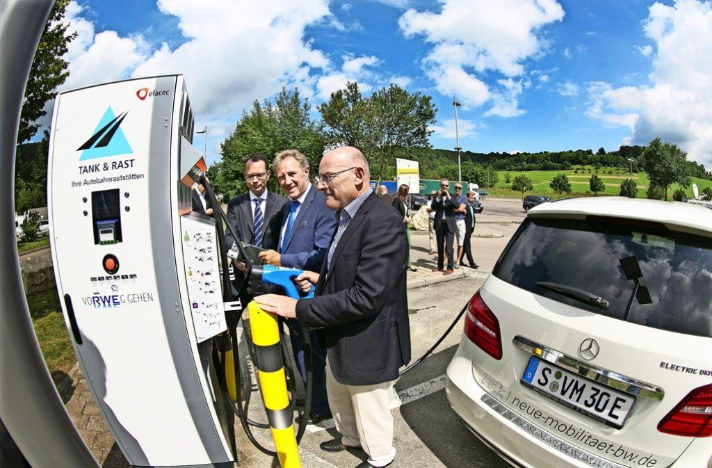 Peter M. Löw, Norbert Barthle und Winfried Hermann (von links) testen die neue Schnellladesäule. Foto: Horst Rudel