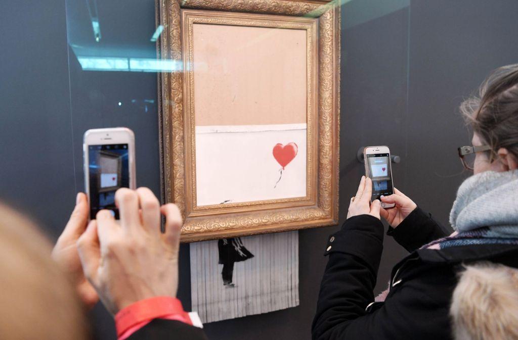 """Besucher lichten das geschredderte Werk """"Love is in the Bin"""" in Baden-Baden mit ihren Smartphones ab. Foto: AFP"""