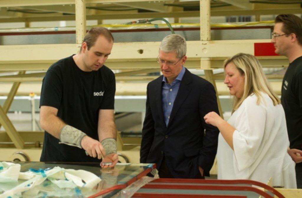 Apple-Chef Tim Cook (Mitte) beim Besuch des Glas-Spezialisten Seele, dessen Tochtergesellschaft Sedak die Frontscheiben des neuen Apple-Hauptquartiers in Cupertino liefert.  Foto: dpa