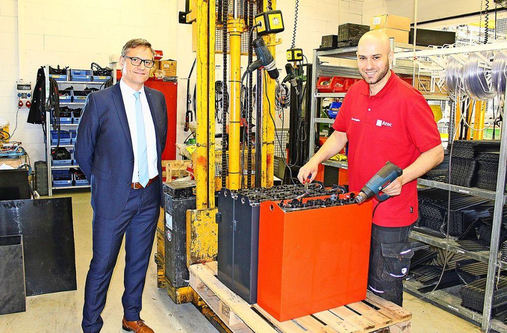 Atec-Prokurist Michael Pape mit Mitarbeiter Antonios Kechagias, der gerade eine Stapler-Batterie aus mehreren Zellen zusammenstellt. Foto: Caroline Holowiecki