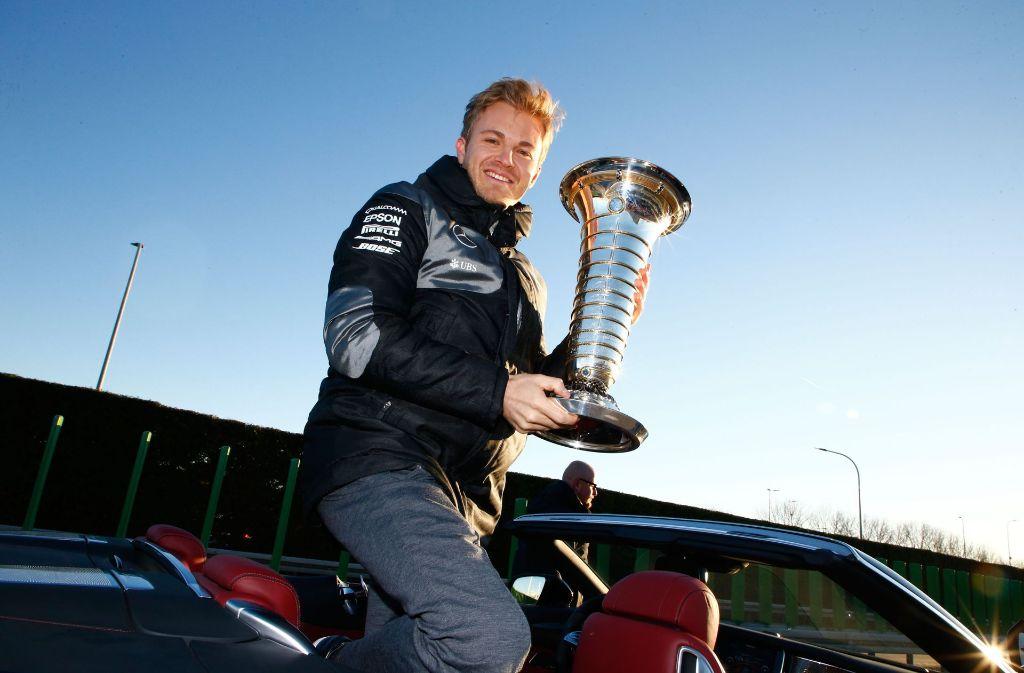 Da ist der Pott: Nico Rosberg zeigt ihn noch einmal im Mercedes-Werk in Sindelfingen. Foto: Mercedes