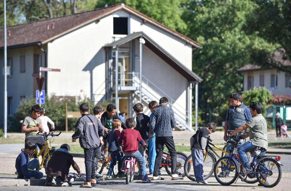 Flüchtlingskinder sind im Patrick-Henry-Village vor einem ehemaligen Kasernengebäude zu sehen, das als Unterkunft dient. (Archivbild) Foto: Uwe Anspach/Uwe Anspach