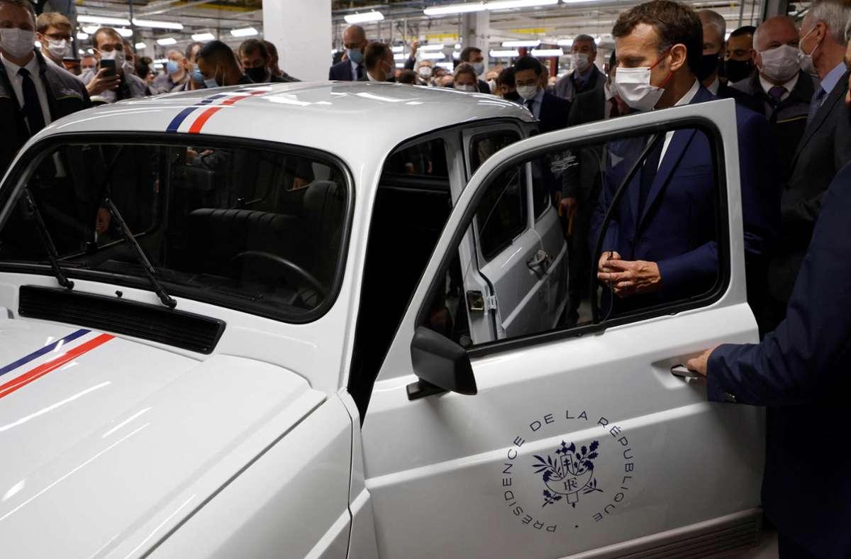 Frankreichs Präsident Emmanuel Macron sieht sich in einem Werk in Douai einen elektrischen Renault 4 an. Bei seinem Besuch in Nordfrankreich verkündet er chinesische Milliardeninvestitionen in einem Batteriefabrik. Foto: AFP/LUDOVIC MARIN