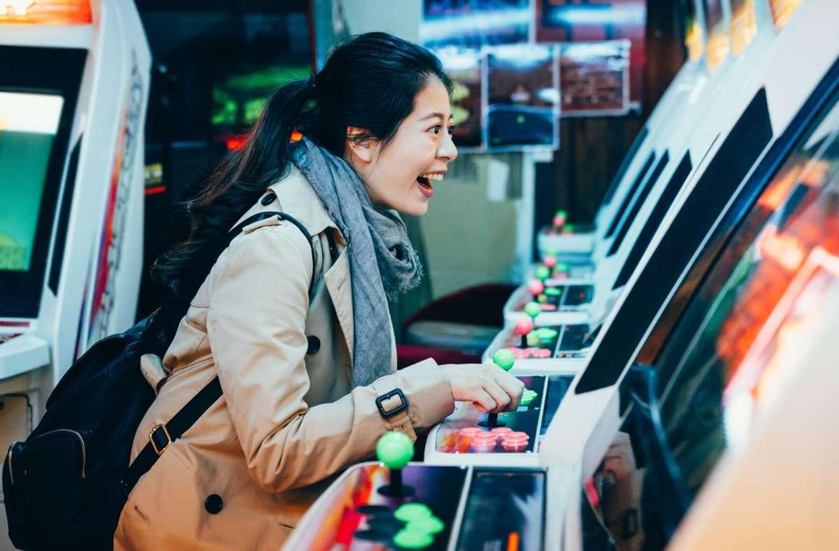 Eine junge Frau aus Osaka hat Spaß am Automaten. Foto: PR Image Factory –  stock.adobe.com/C.Y.Ronnie.W