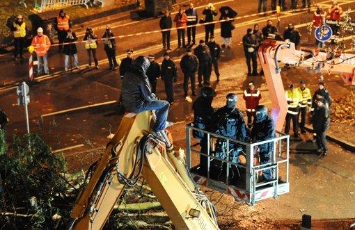 Ein Gegner des Bahnprojekts Stuttgart 21 wird am Sonntag (22.01.2012) von Sondereinsatzkräften der Polizei in Stuttgart von einem Bagger geholt. Unter Protest begannen im Bereich des Wagenburgtunnel die Fällung von 31 Bäumen. Foto: Franziska Kraufmann dpa/lsw  +++(c) dpa - Bildfunk+++ Foto: dpa