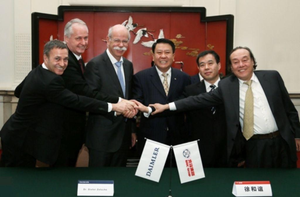 Dieter Zetsche und Xu Heyi (Mitte) wollen, dass ihre Konzerne zusammenrücken. Foto: dpa