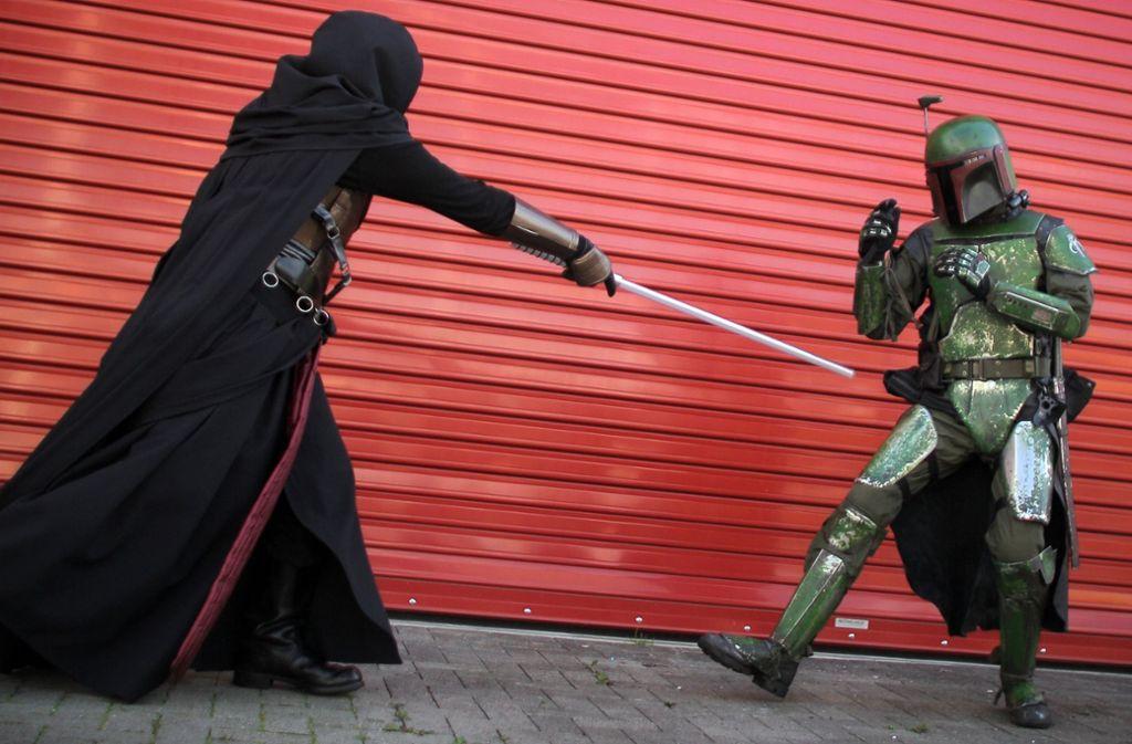 Ein als Darth Raven und ein als Boba Fett verkleideter Fan duellieren sich (Symbolbild). Foto: dpa