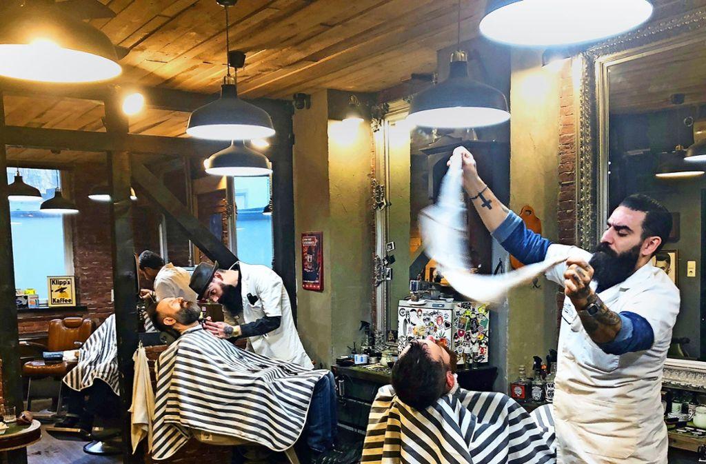 Janni Chronakis  (rechts) sieht sich als Barbier der alten Schule. Er betreibt den Barbershop Jack the Ripper an der Hackstraße. Die Neugründungen in seinem Metier sieht er kritisch. Foto: jc