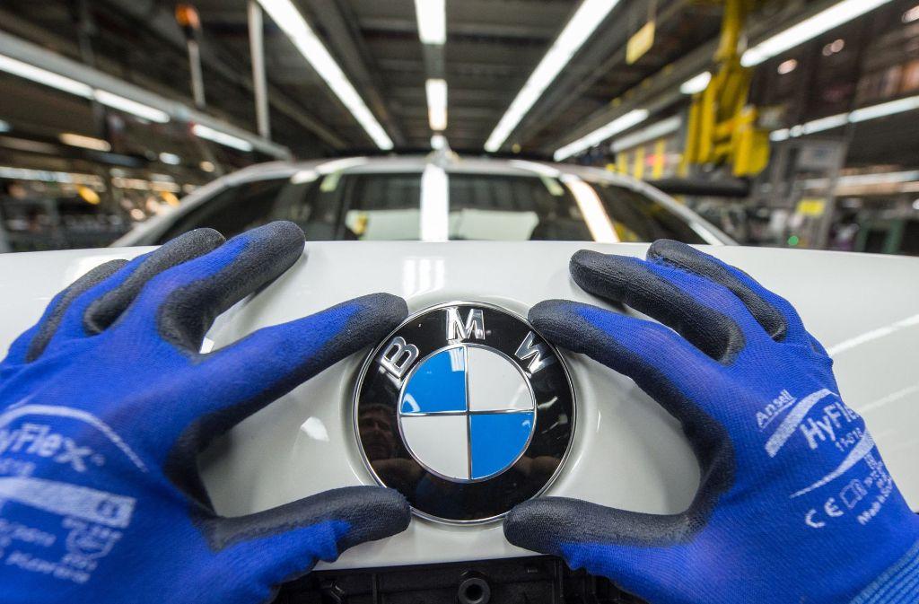 Bei BMW sprudelt der Gewinn. Hier ein Blick in die Montage im Werk Dingolfing, wo ein   BMW-Emblem am Kofferraumdeckel angebracht wird. Foto: dpa