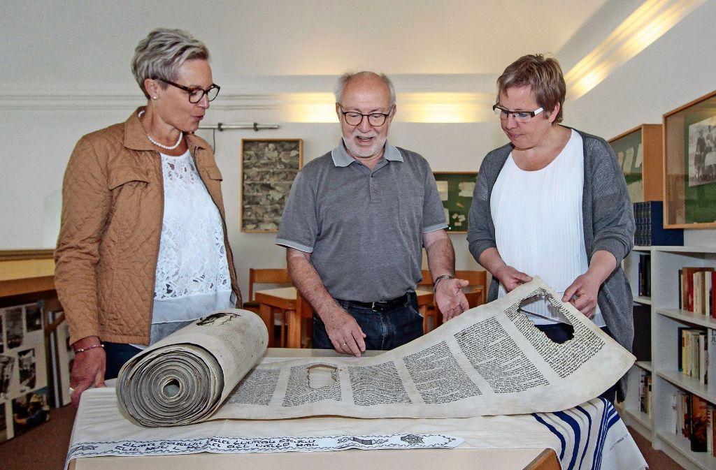 Isolde Siegers, Herbert Pötzsch und Barbara Schüßler (von links) mit einer teilweise zerstörten Schriftrolle Foto: factum/Bach