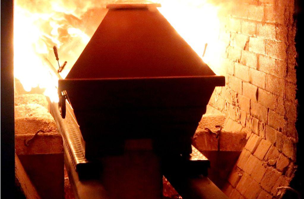 Ein Sarg wird in den rund 850 Grad heißen Ofen eines Krematoriums in Essen (Nordrhein-Westfalen) gefahren. Foto: Roland Weihrauch/dpa