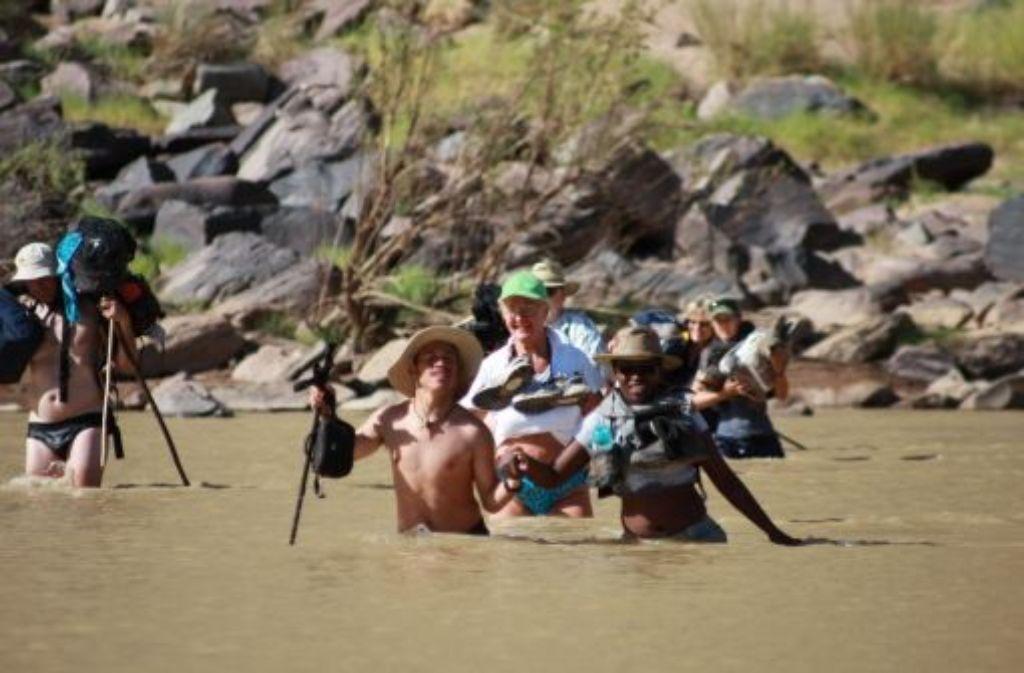 Wenn's neben dem Fluss nicht weitergeht, dann halt mitten hindurch: Tourführer Manilow (vorn Mitte) durchquert mit seiner Wandergruppe den Fischfluss. Foto: Peter-Michael Petsch