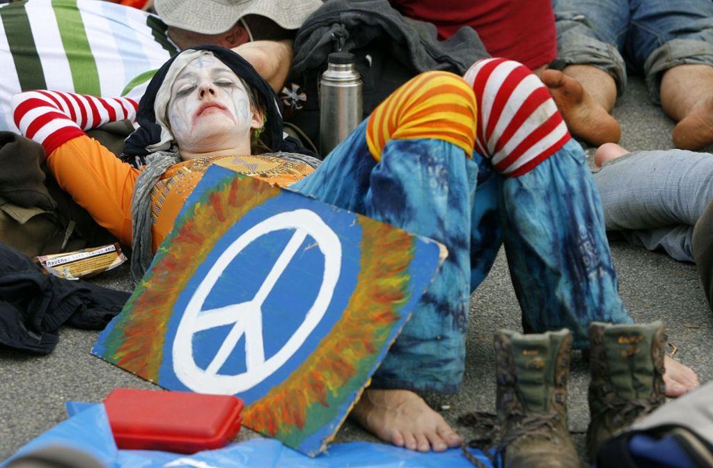 Eine Frau liegt mit einem selbst gemalten Peace-Zeichen auf dem Boden. Überall auf der Welt kennt man das Symbol. Foto: dpa