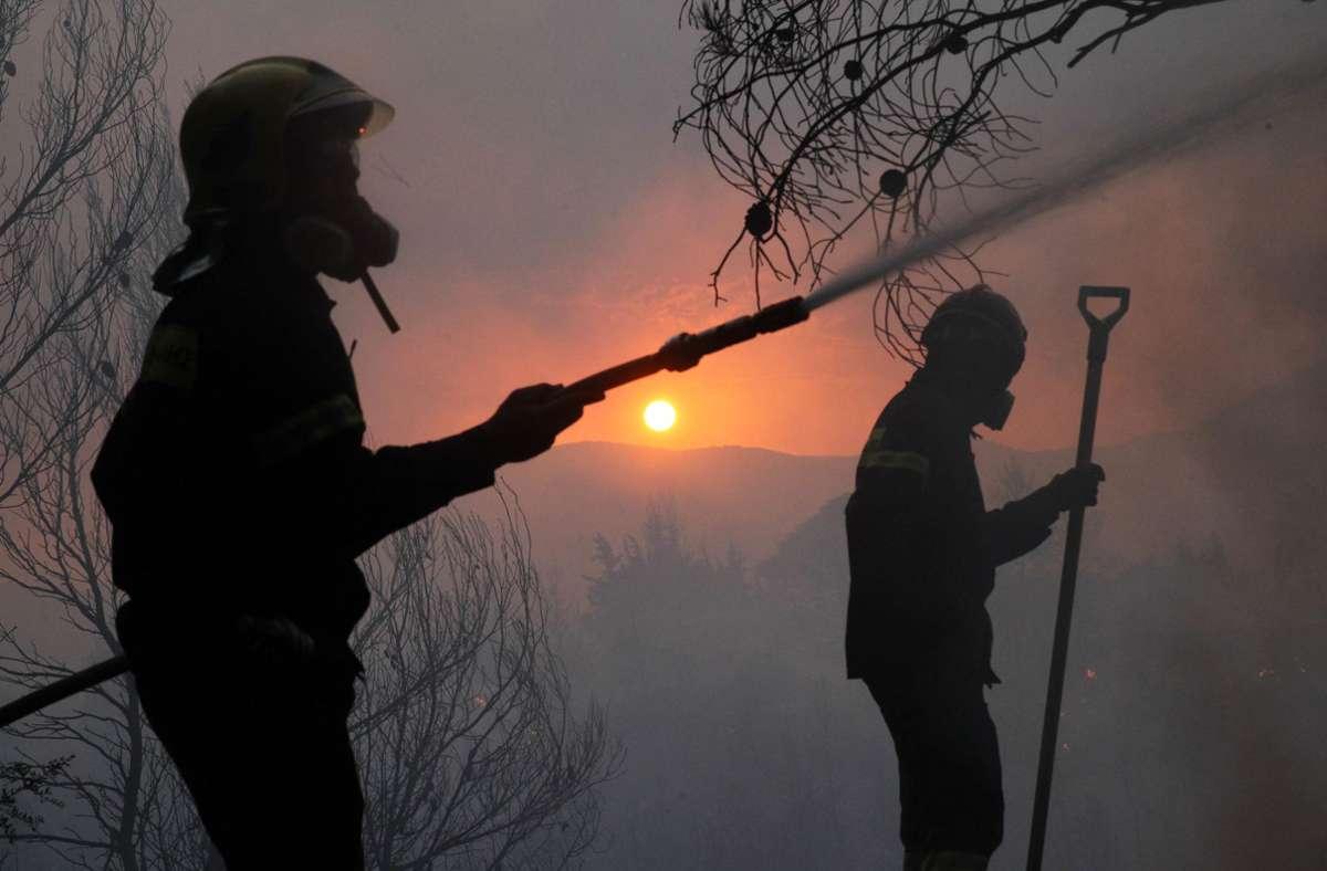 Feuerwehrleute kämpfen gegen den Waldbrand, der am Dienstag auf Vororte von Athen übergegriffen hat. Foto: dpa/Marios Lolos