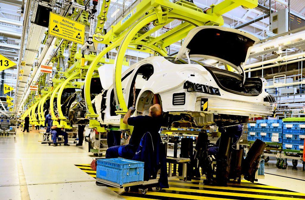 Mitarbeiter im Mercedes-Benz-Werk in Sindelfingen (links):   In einem  Pilotprojekt  in  Stuttgart-Untertürkheim, Bremen und Kassel zahlte Daimler denjenigen Beschäftigten Geld,  die nur selten gefehlt hatten.  Der Versuch könnte bald  konzernweit zur Regel werden. Foto: dpa
