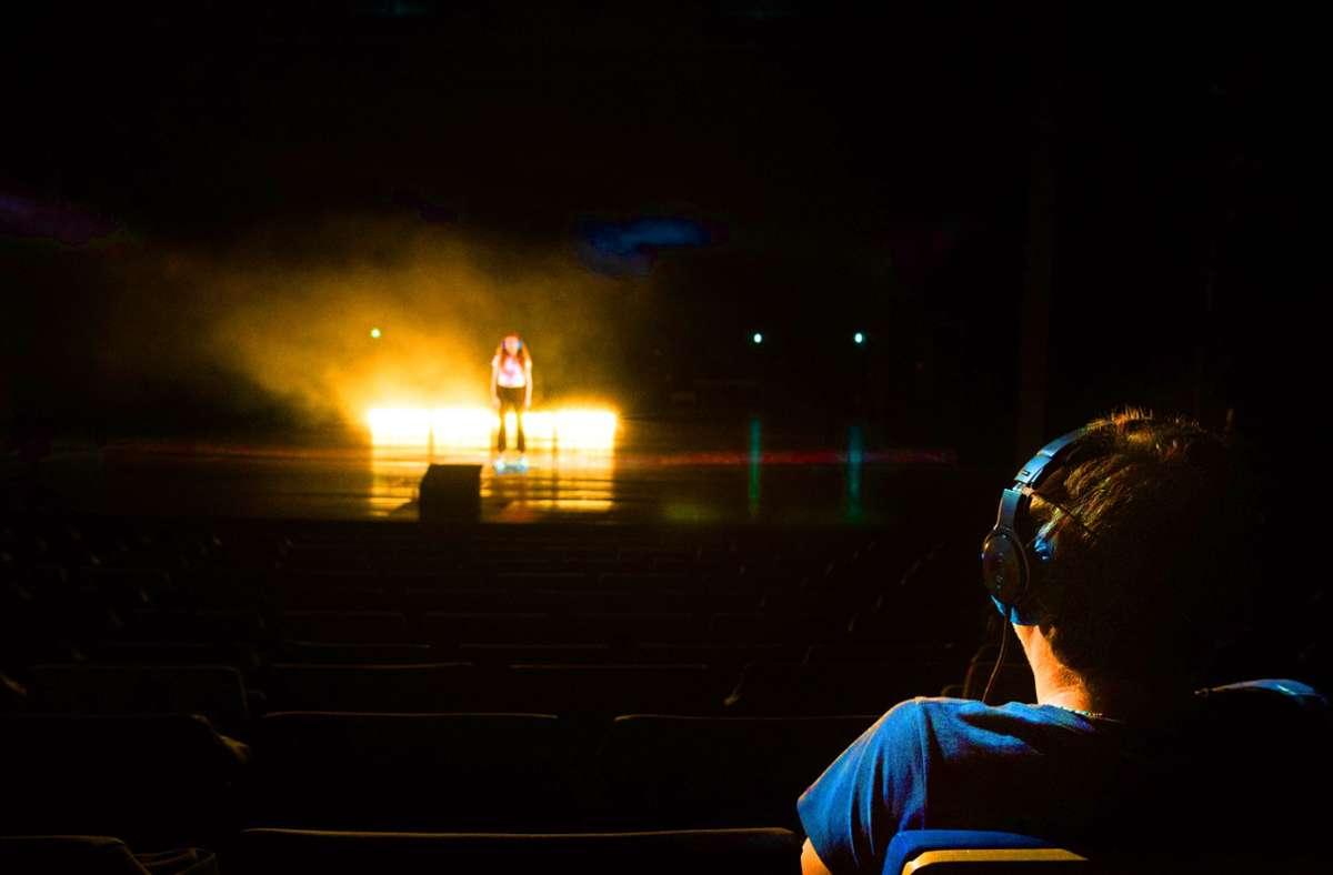 """Der  Zuschauer   als Mitmacher: Ein Teilnehmer des Theaterparcours  """"Black Box"""" von Rimini Protokoll sitzt im Saal und  einer steht auf der Bühne. Text hören beide via Kopfhörer. Foto: Björn Klein"""