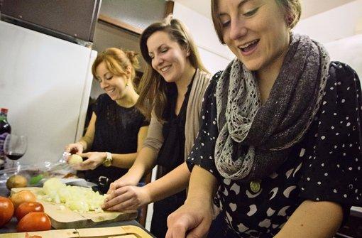 Noch vor einer Stunde haben sie sich nicht gekannt – und schon werkeln sie gemeinsam in der Küche: Foto: Michael Steinert