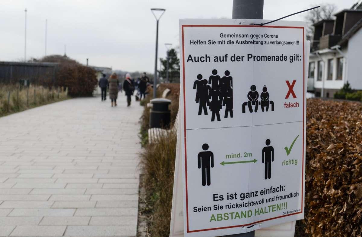 Ein Schild auf einer Promenade in Schleswig-Holstein weist auf Corona-Regeln hin. Foto: Frank Molter/dpa