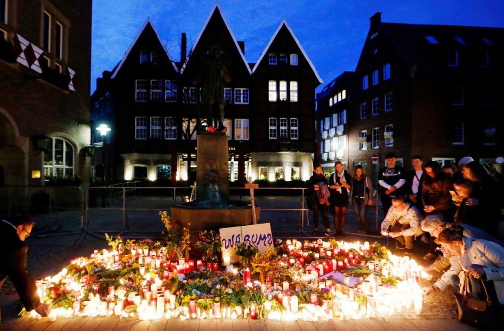 Menschen gedenken mit Kerzen der Opfer der Amokfahrt von Münster. Foto: dpa