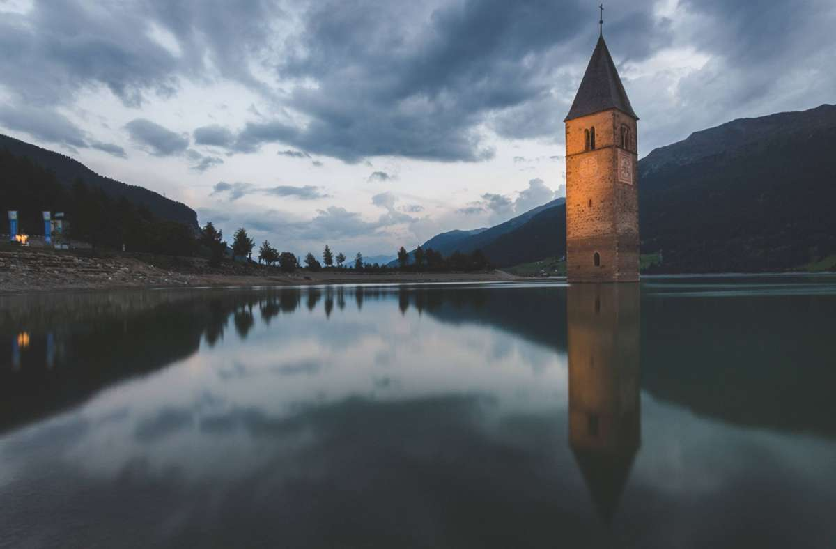 Südtirol-Touristen kennen den Reschensee mit seinem markanten, versunkenen Kirchturm. Foto: imago images/UIG