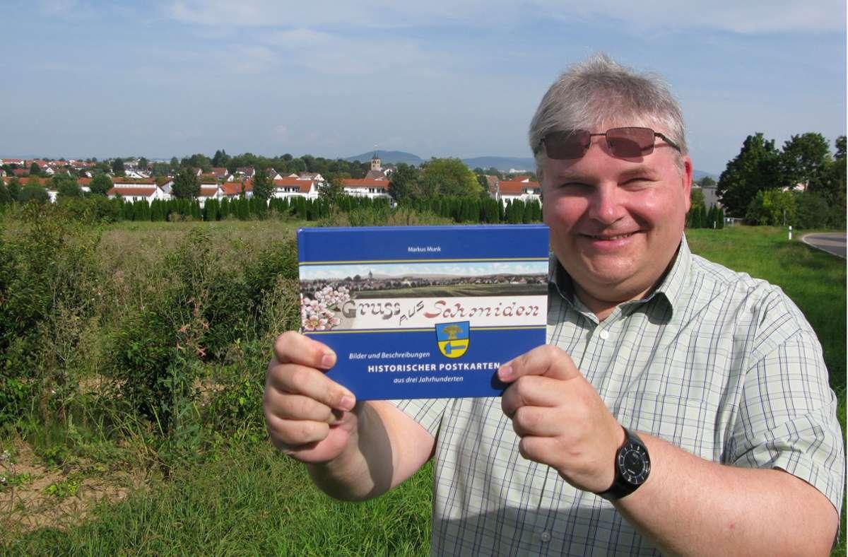 Markus Munk mit seinem neuen Postkartenbuch vor der Silhouette Schmidens Foto: Eva Schäfer