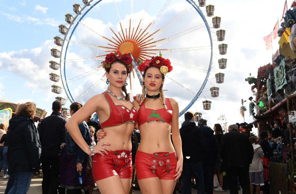 Die Models Marie S. (l) und Julia Gashi tragen bei warmem Oktoberwetter Dirndlbikinis auf dem Oktoberfest vor dem Riesenrad. Foto: dpa/Felix Hörhager