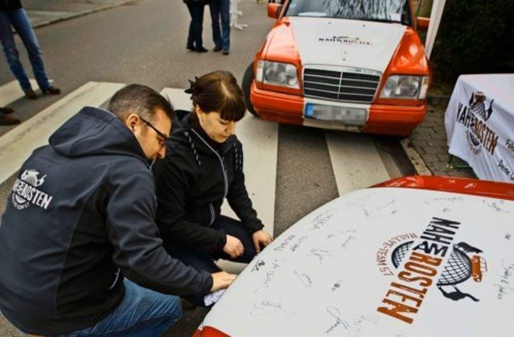 An den Rallye-Fahrzeugen werden noch die letzten Aufkleber angebracht Foto: Gottfried Stoppel