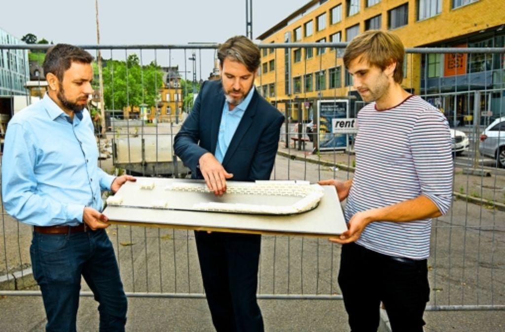 Markus Benz vom Stadjugendring, der Architekt Tracy Krüger und Christoph Mack von der Projektgruppe Tante Gerda (von links)  stellen am ehemaligen ZOB  die erste Möblierung – eine Tribüne  aus Europaletten –  vor. Foto: Horst Rudel