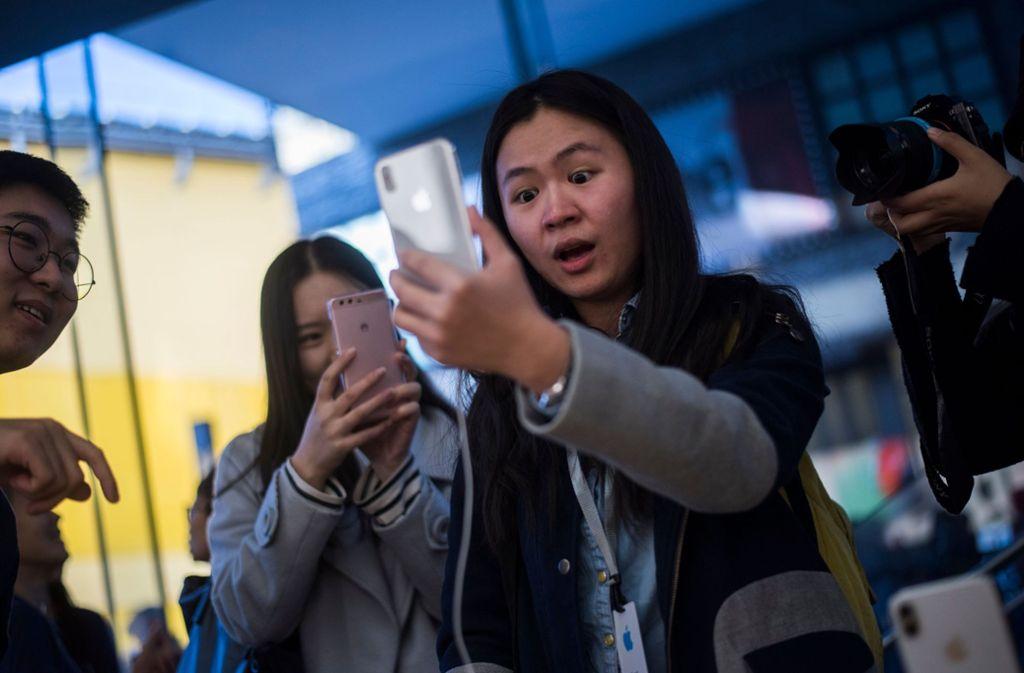 """Deutschland hinkt technologisch hinterher: In Peking können iPhone-Besitzer bereits per Gesichtserkennung  bezahlen – der Dienst nennt sich """"Smile to Pay"""" (""""Lächle zum Bezahlen""""). Diese Kundin tut sich mit dem Lächeln ganz offensichtlich schwer. Foto: AFP"""