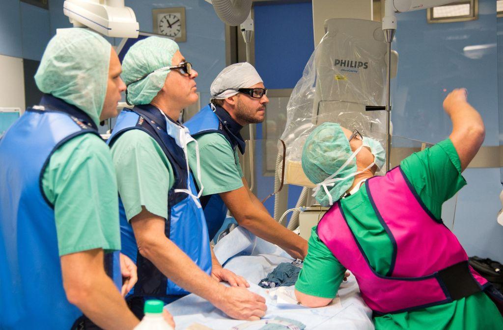 Während Oberarzt Mirko Zimmermann (hinten rechts) den OP-Draht einführt, geht der Blick zum Monitor, auf dem der feine Draht genau zu sehen ist. Foto: Lichtgut/Oliver Willikonsky