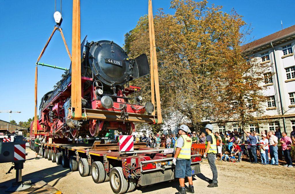Unter großer Anteilnahme wird die alte Dampflok auf den Tieflader gehievt und wartet dann tagsüber  an der Poststraße auf den Weitertransport zum Märklin-Museum. Foto: Horst Rudel