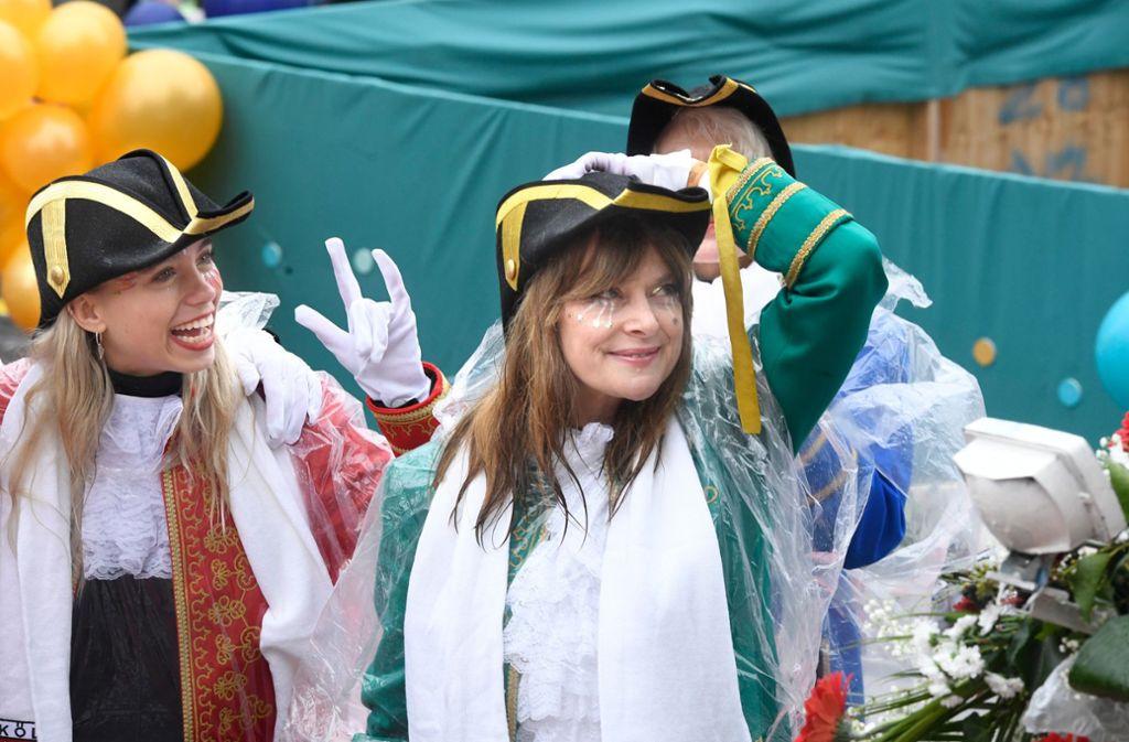 Die Schauspielerin Nastassja Kinski (59) hat vom Karnevalswagen des Festkomitee-Präsidenten aus beim Rosenmontagsumzug in Köln Winke-Winke gemacht und Kamelle geworfen. Unterstützt wurde sie dabei von einer Hälfte des bekannten Influencer-Zwillingspaars Lisa und Lena. Foto: dpa/Roberto Pfeil