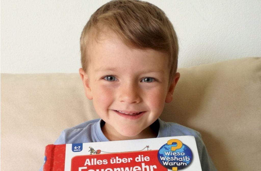 Der vierjährige Tobias Neuner aus Saulgrub im Landkreis Garmisch-Partenkirchen zeigt sein Kinderbuch zum Thema Feuerwehr Foto: Anna Elisabeth Neuner/dpa