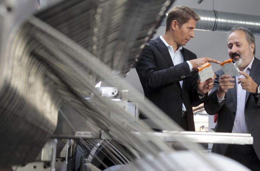 Kunbus-Gründer Martin Kunschert (links) und Projektleiter Volker de Haas vor einem Fertigungsautomaten für Platinen. In der Hand halten sie ihr neuestes, innovatives Bauteil. Foto: factum/Weise