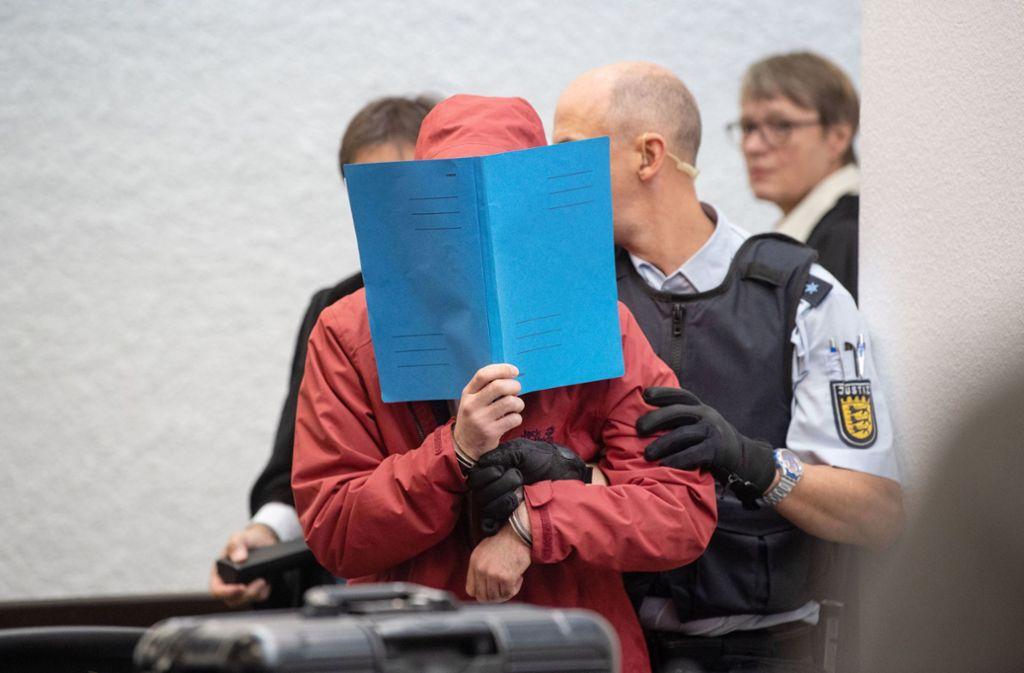Der Angeklagte hat den Gerichtssaal hinter einer Mappe verborgen betreten. Foto: dpa
