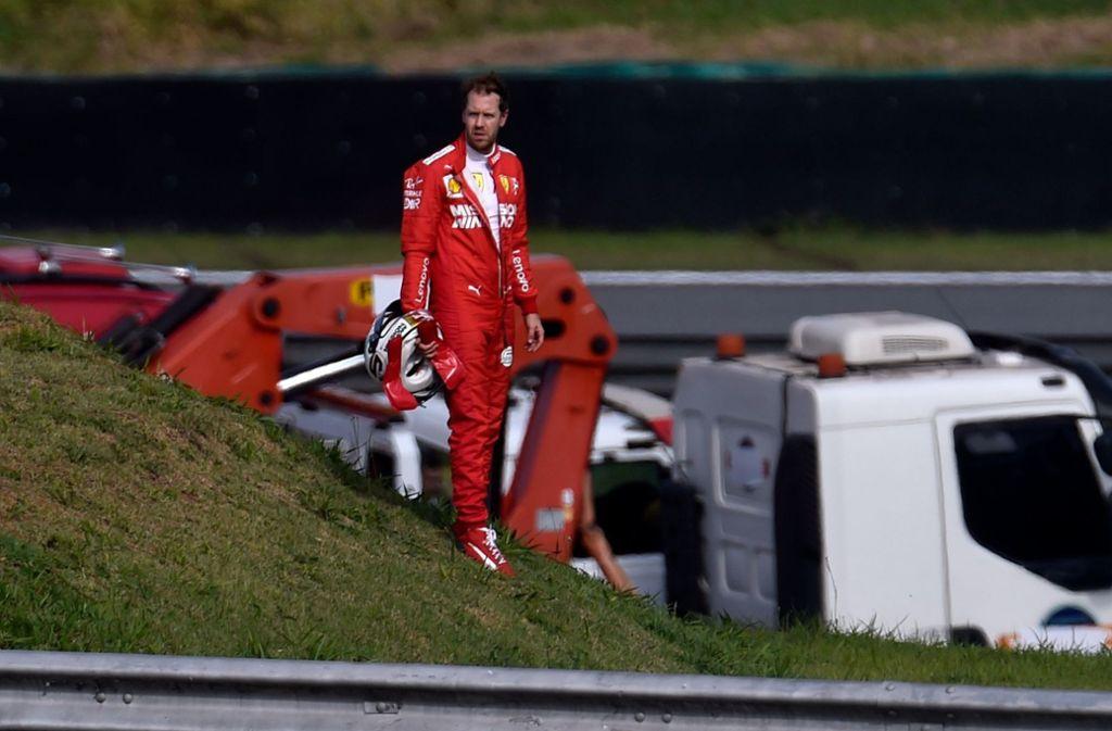 Sebastian Vettel steht nach seinem Crash enttäuscht an der Rennstrecke. Foto: AFP/DOUGLAS MAGNO