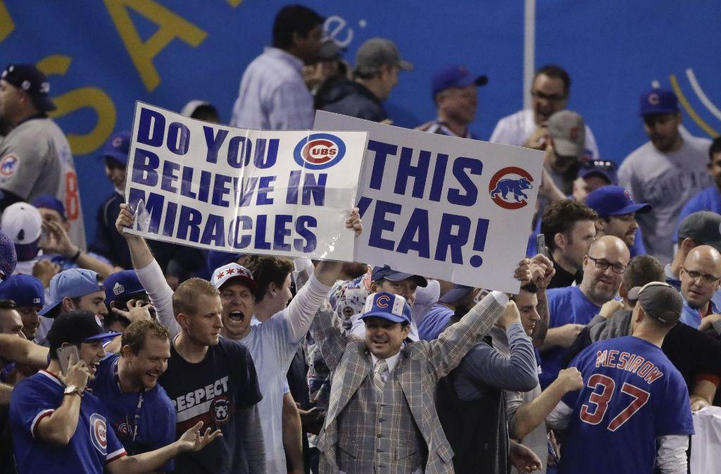"""""""Glaubst Du an Wunder? – Dieses Jahr!"""", steht auf dem Plakat der Cubs-Fans, die im Wrigley-Field in Chicago feiern. Foto: AP"""