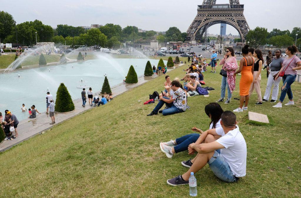 Touristen und Einheimische sitzen  am Brunnen im Jardin du Trocadéro in Paris. Foto: dpa