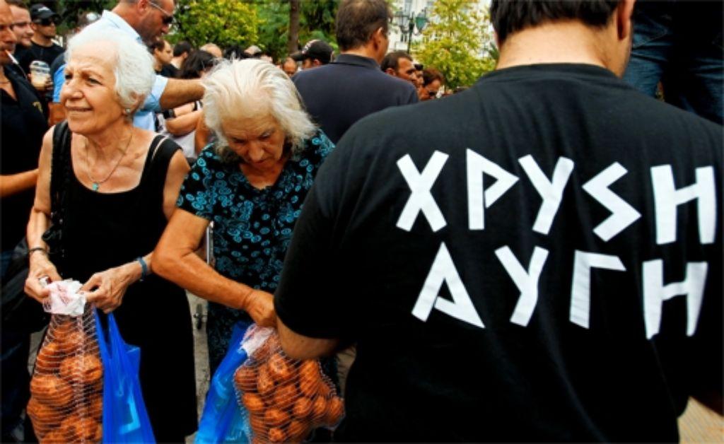 """Mitglieder der """"Goldenen Morgendämmerung"""" verteilen Lebensmittel. Foto: dapd"""