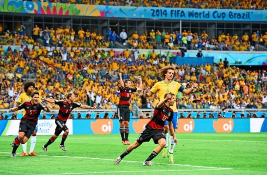 Der Anfang vom Ende für die bedröppelten Brasilianer: Thomas Müller  (rechts vorne)  erzielt das 1:0 und eröffnet damit das  Schützenfest der stürmischen Deutschen in Belo Horizonte. Weitere Eindrücke vom Spiel gibt es in der Bilderstrecke. Foto: dpa
