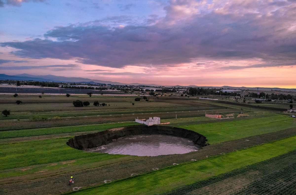 Auf einem Feld bei dem Ort Santa Maria Zacatepec ist der  mit Wasser gefüllte Krater zu sehen. Foto: Karlos Pinpunk/dpa/Karlos Pin-Punk