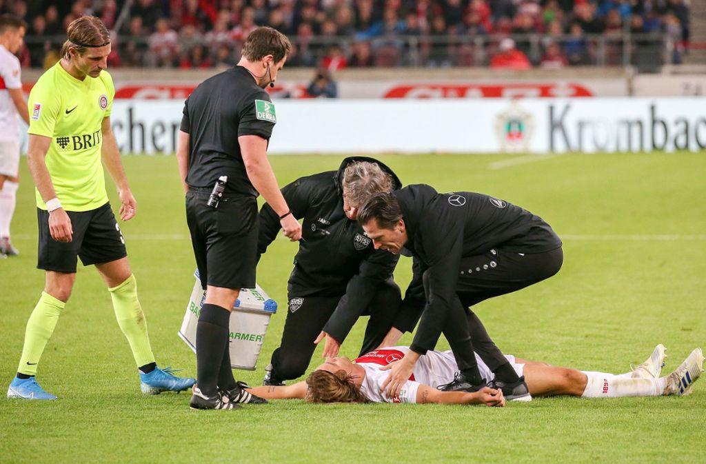 Borna Sosa liegt regungslos am Boden – der VfB-Mannschaftsarzt Heiko Striegel (rechts) und der Physiotherapeut Gerhard Wörn kümmern sich um ihn. Schiedsrichter Johannes Pfeifer und der Wiesbadener Stefan Aigner (rechts) schauen zu. Foto: Baumann