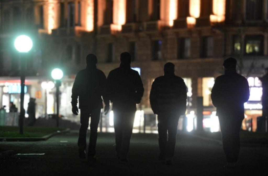 """Vier Mitglieder der Gruppe """"Stuttgart passt auf"""" spazieren am Samstagabend durch die Innenstadt. Foto: dpa"""