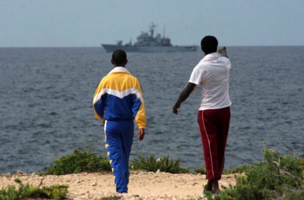 Warten auf Hilfe: zwei Flüchtlinge an der Küste von Lampedusa Foto: ANSA