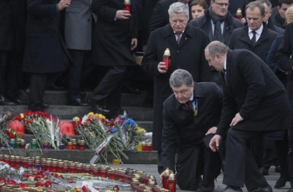 Neben Präsident Poroschenko (kniend) hat auch  Bundespräsident Joachim Gauck eine Kernze zur Erinnerung an die  Toten des Maidan-Protestes vor einem Jahr angezündet. Foto: