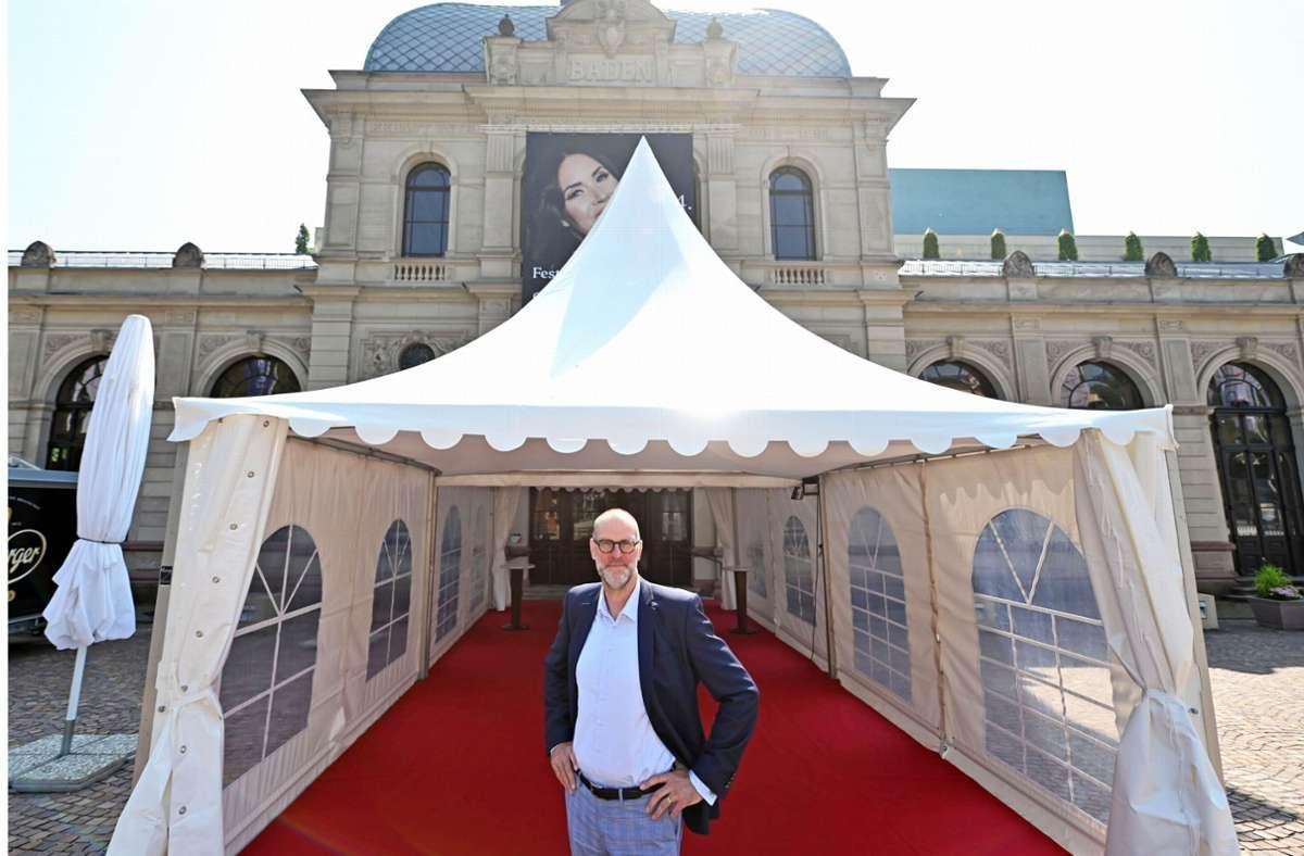 """Das Festspielhaus in Baden-Baden setzt auf """"Fliegende Bauten"""", um Abstände auch bei Regen zu sichern. Intendant Benedikt Stampa steht in einem solchen Zelt  vor dem Haupteingang. Foto: dpa/Uli Deck"""