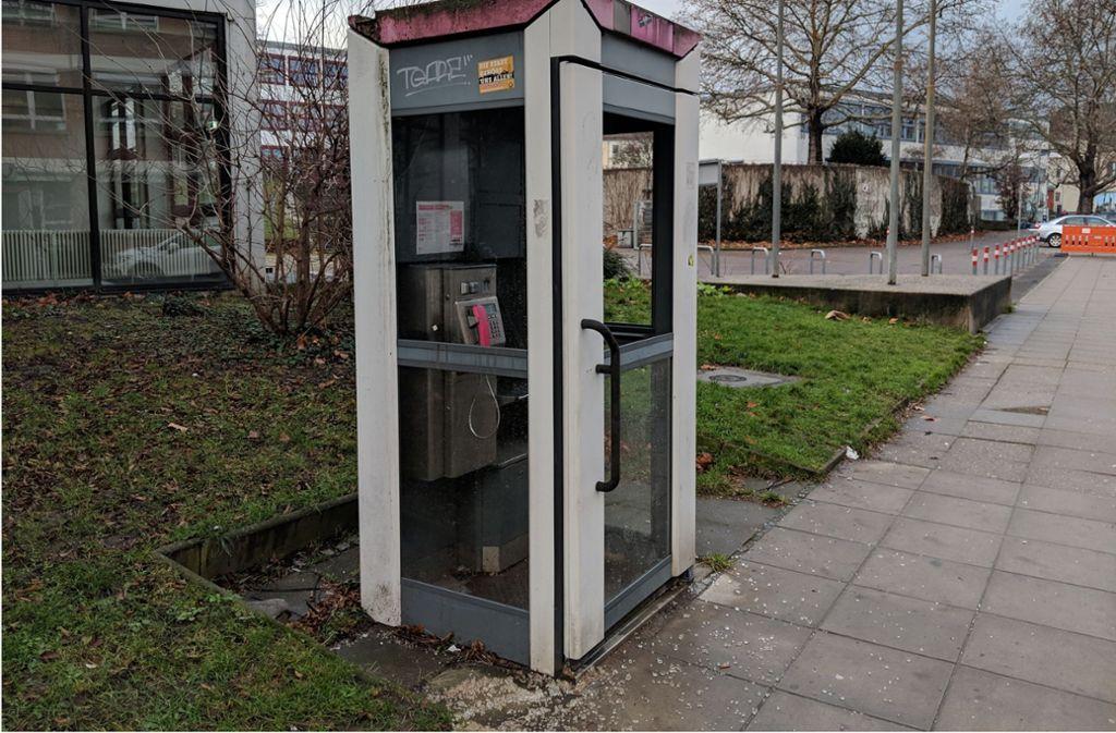 An dem Telefonhäuschen an der Schönbühlstraße sind zwei der neuen  Scheiben zertrümmert, die Scherben liegen noch am Boden. Foto: Jürgen Brand