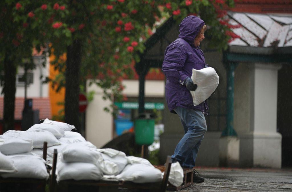 Eine Frau nimmt sich nahe des Flusses Argen Sandsäcke, die für die Anwohner bereitgestellt wurden. Foto: dpa