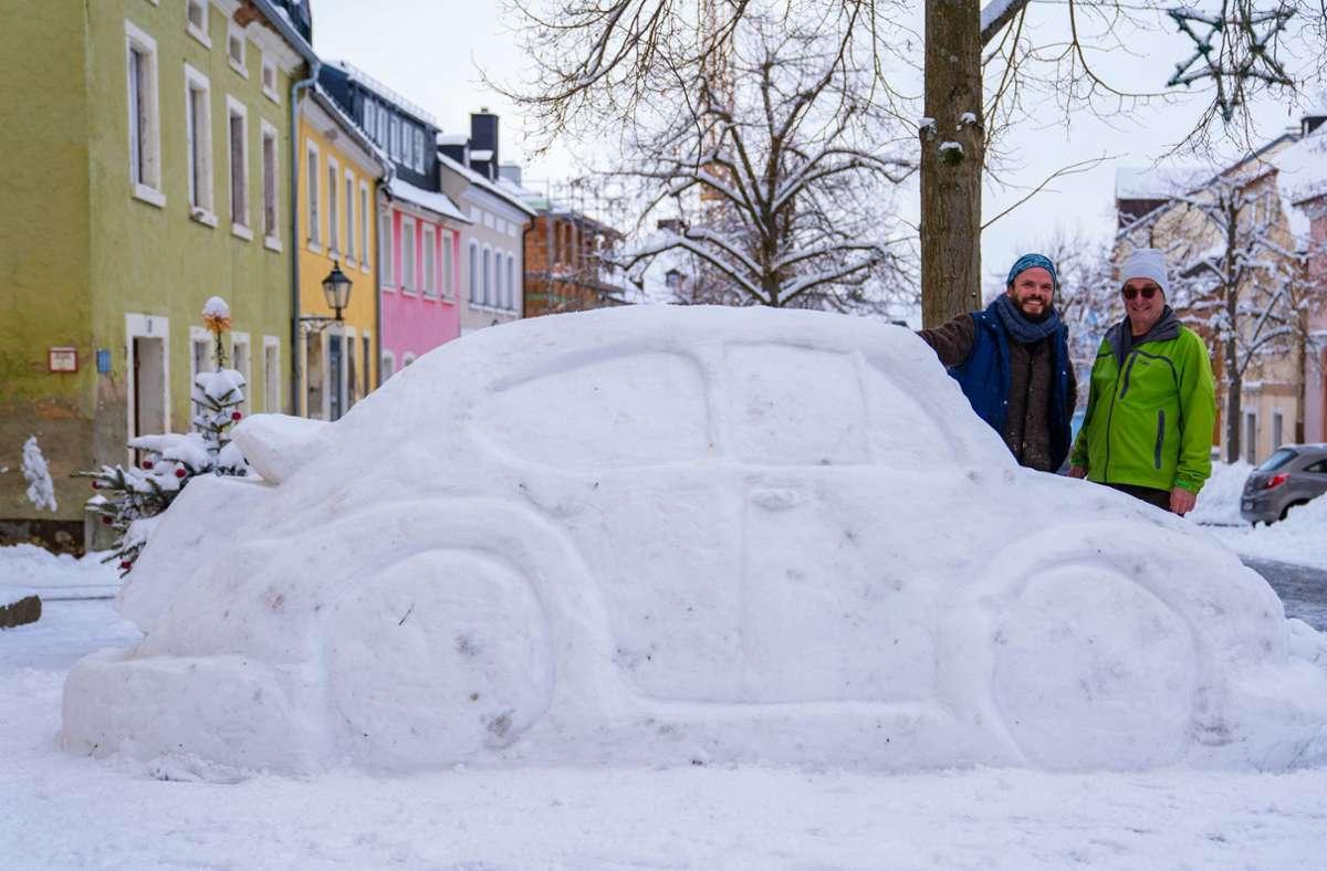 """Eberhard Burger (rechts) und sein Nachbar Stefan Parnt stehen neben ihrem aus Schnee erbauten """"Käfer"""". Foto: dpa/Nicolas Armer"""