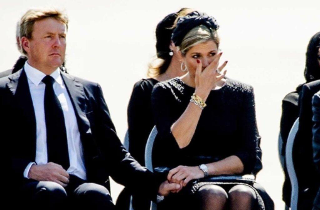 Königin Máxima wischt ihre Tränen ab, König Willem-Alexanders Miene ist versteinert: Am Flughafen von Eindhoven empfängt das niederländische Königspaar die Toten des abgeschossenen Fluges MH17. Foto: dpa